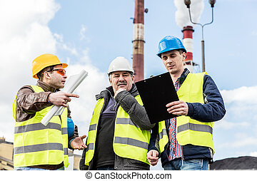 Construction engineers examining thermoelectric power...