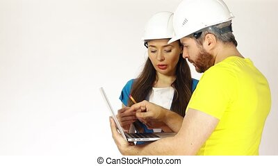 Construction engineers or architects discuss project and use the laptop