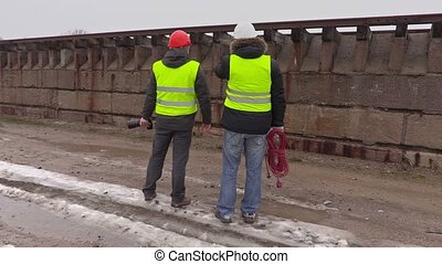 Construction engineers talking near wall