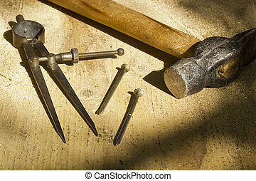 A hammer laying next to nails and a drafting compass with selective focus and selective light.