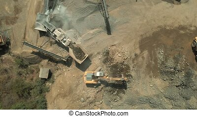 Construction equipment working at quarry. Heavy machinery works at industrial quarry. View from above.