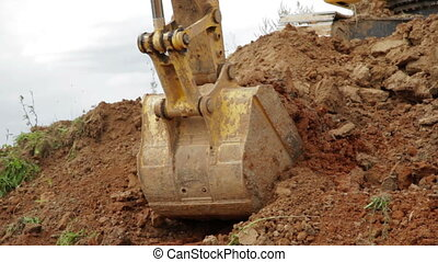 Construction Excavator Scooping and Dumping on Dirt Pile or...