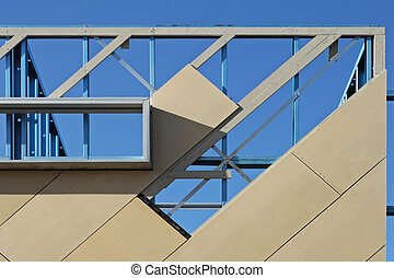 Wall of the constructed house with window partly covered with decorative facing panels in sunny day on clean blue sky