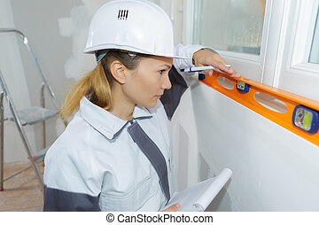construction female worker with level tool on house wall