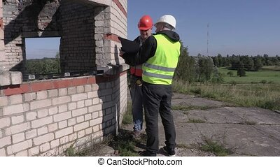Construction foreman and worker talking with each other