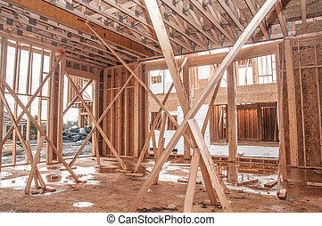 Unfinished house construction frame under rain