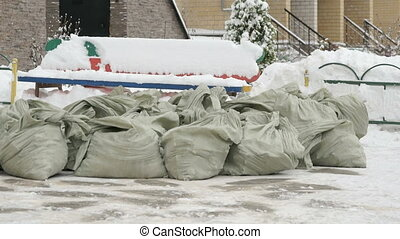 Construction garbage in bags lying in the snow next to the...