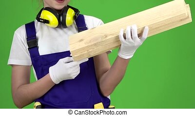 Construction girl in a helmet wiping the dust of three wooden boards. Green screen. Slow motion. Close up