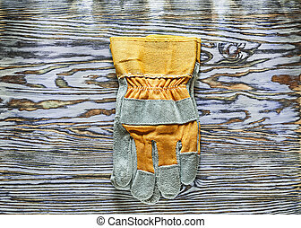 Construction gloves on wooden board