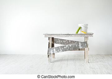 Construction grunge ladder, paint roller and paint bucket in white interior: white wall and gray floor. Apartment decoration concept.