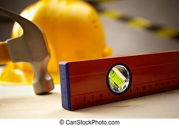 industrial concept with level, hammer and yellow hardhat, selective focus