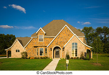 A beautiful two story home with a green lawn and a beutiful blue sky. Real esate concept