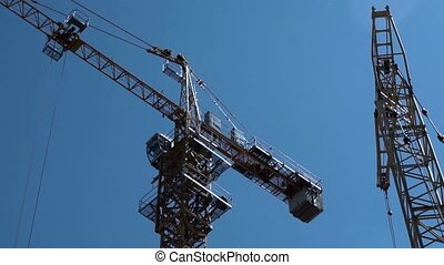 Construction Industry. Crane Working on the Background of Blue Sky.