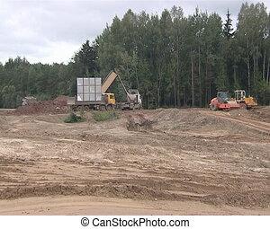 Construction industry. Heavy duty trucks. Truck dumps earth....