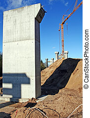 construction industry building infrastructure. motorway bridge architecture with crane and concrete pillars