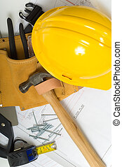 Items used by a construction worker including a leather tool belt, a hammer, a tape measure, tools, floor plans and a yellow hard hat