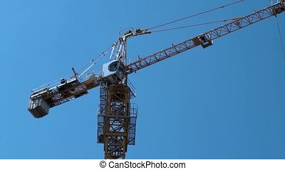 Construction Industry. Tower Crane Working Against Blue Sky