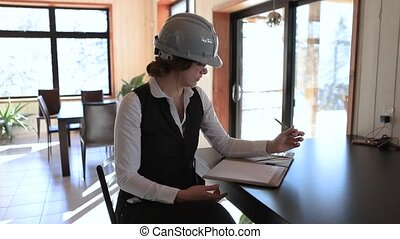 a young attractive female inspector sitting at the table taking notes during home interior inspection then she is smiling and giving a thumbs up.