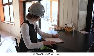 female inspector sitting at the table taking notes during home interior inspection. caucasian woman wears safety grey hard hat and protective glasses.