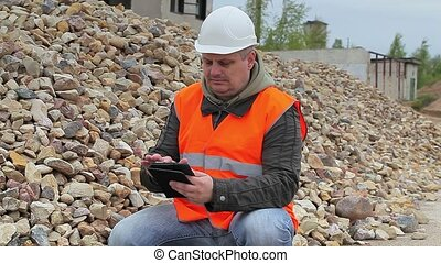 Construction inspector with tablet PC near crushed stone