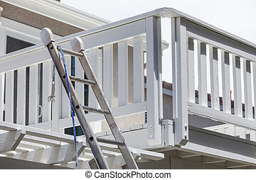 Construction Ladder and Painting Hose Leaning on White House Deck.