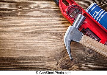 Construction level blue blueprint claw hammer on vintage wood board.