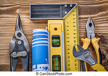 Construction level blueprint try square gripping tongs steel cutter monkey wrench on wood board.
