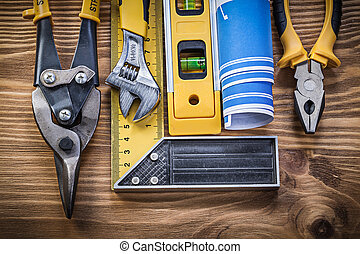 Construction level blueprint try square pliers steel cutter monkey wrench on wood board.