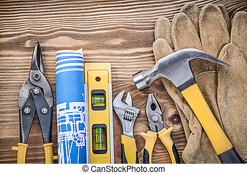 Construction level plan safety gloves claw hammer gripping tongs steel cutter adjustable wrench on wooden board.