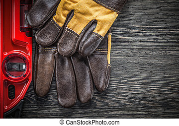 Construction level working gloves on wooden board