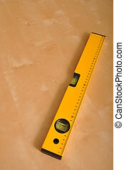 yellow construction level on a brown wooden background