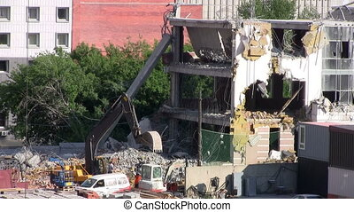 Construction machinery destroys an old building