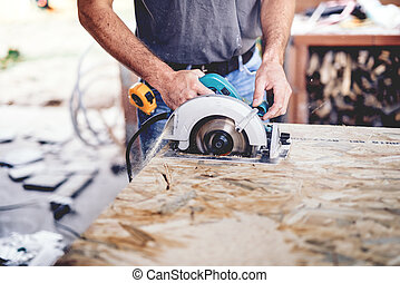 Construction man working with a chop saw in wood workshop. Details of wood cutting using circular saw