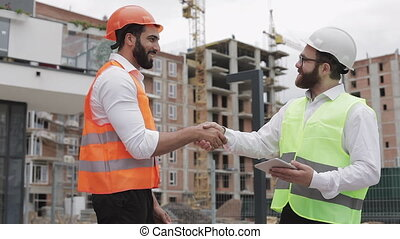 Construction manager and workers shaking hands on...