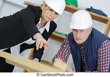 construction manager instructs a subordinate in the workplace