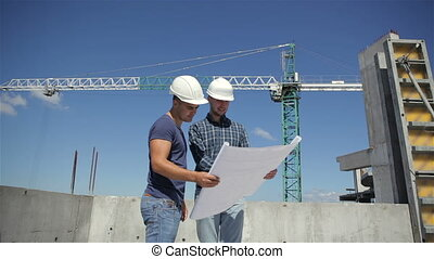 Construction manager points at the plan of building under...
