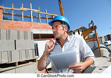 Construction manager using electronic tablet on building...