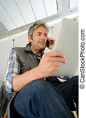 Construction manager using mobile phone on building site