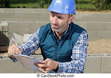 construction manager writing report at construction site