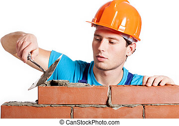 Construction mason installing red brick