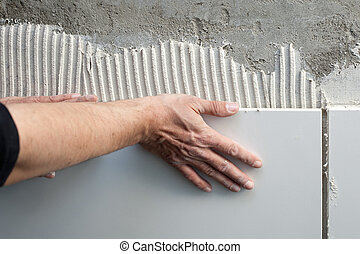 construction mason man hands on tiles work with notched...