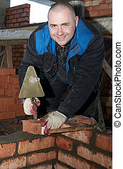 construction mason worker bricklayer checking a brickwork with level tube