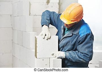 construction mason worker bricklayer installing calcium ...