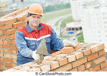 construction mason worker bricklayer installing red brick ...