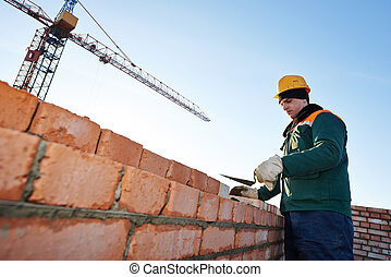 construction mason worker bricklayer installing red brick ...