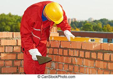 construction mason worker bricklayer making a brickwork with...