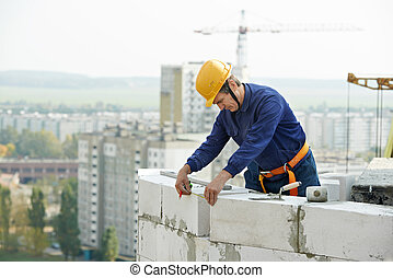 construction mason worker bricklayer working with limestone...