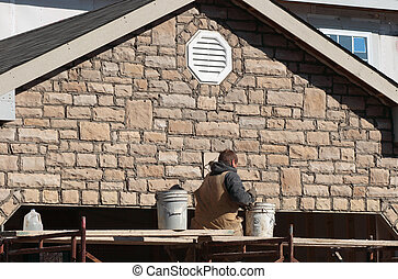 Construction Masonry - Stone mason pointing stone on a...