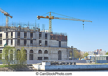 Construction of a dwelling house, cranes, working builders