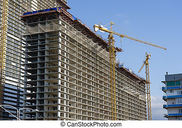 Construction of a high-rise building with a crane. The construction crane and the building against the blue sky.